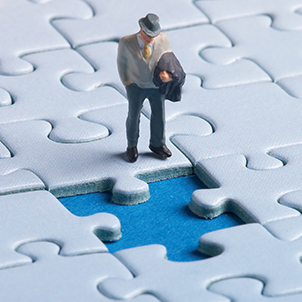 A photograph of a plastic figure standing in front of a hole in a jigsaw puzzle.